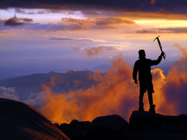 Climbing Silhouette of man at top of mountain at dusk