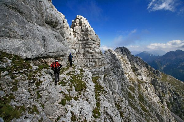 Camp and Hike Picture of two hikers on the side of mountain in the Julian Alps