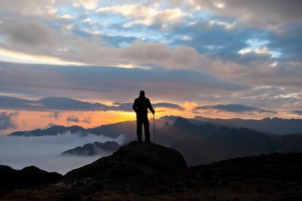 Camp and Hike Picture of a man standing at Mount Kilimanjaro at sunset