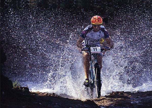MTB Mountain bike racer splashes through a puddle.