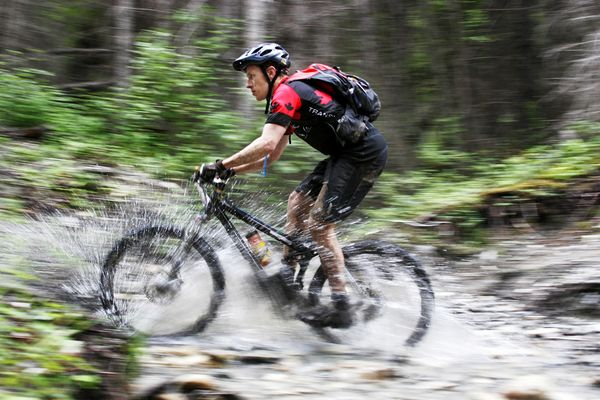 MTB Transrockies Canada race contestant rides through a puddle.