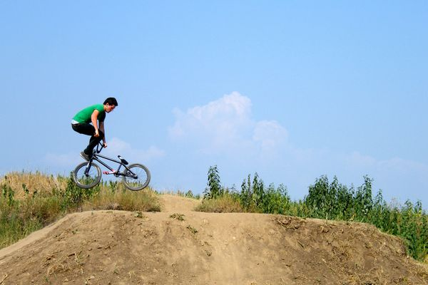 BMX Rider jumping over hill on dirt track.