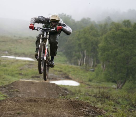 MTB Bike rider jumping over a hill.