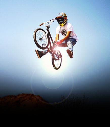 BMX BMX rider performing an air trick over a dirt mound in Las Vegas, Nevada.