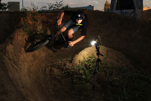 BMX Night rider rounds a curve.