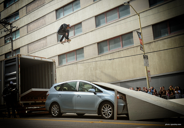 Skateboard ollieing over a Prius