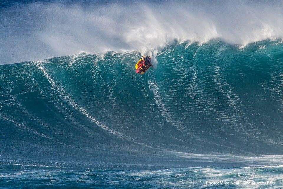 Surf Ian Walsh surfing Peahi on a giant inflatable hotdog.