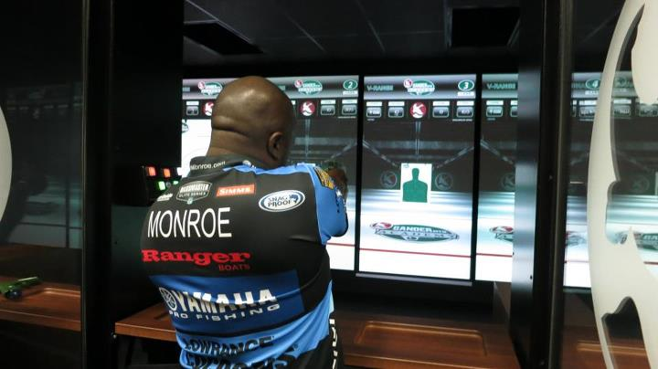 Ish Monroe testing the shooting range simulator in the Gander Mountain Academy