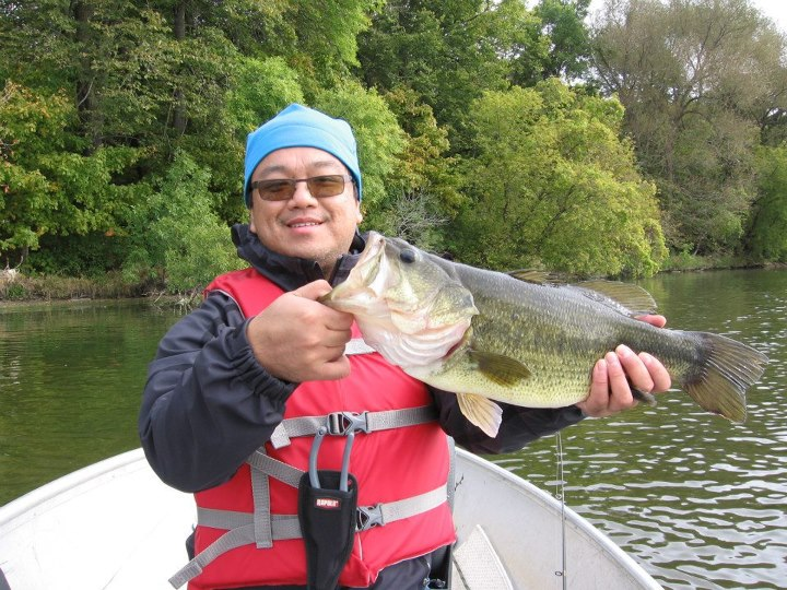 "Entertainment Sang Vo tells us:  ""This largemouth was pulled out of a Minnesota lake on a Booyah Pad Crasher.  We were trolling for northern when we stopped near the shore for a break to eat. I pointed to some low overhanging trees along the shore and said to my fishin"