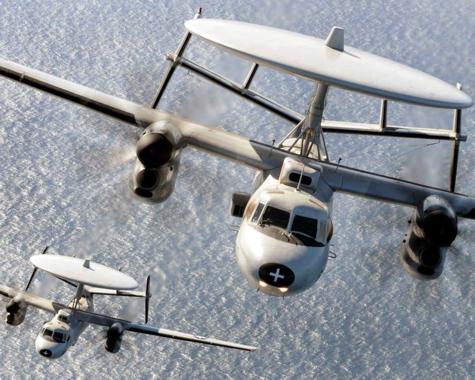 Guns and Military E-2C Hawkeye aircraft assigned to the Wallbangers of Carrier Airborne Early Warning Squadron (VAW) 117 fly over the Pacific Ocean near Ventura, Ca.