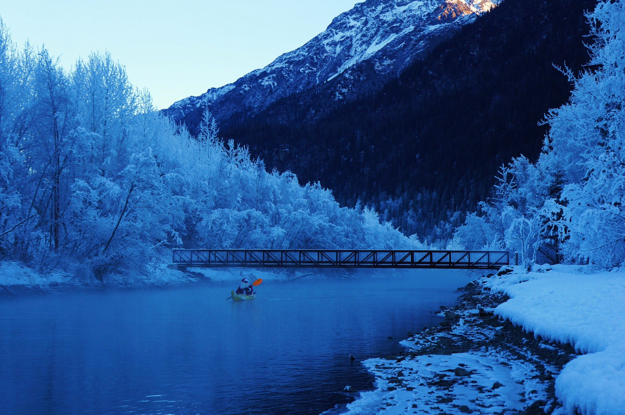Kayak and Canoe Santa paddling his Looksha on the Eklutna Tailrace in Alaska at minus 4 degrees