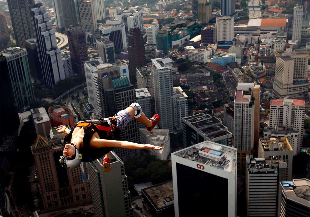 Extreme base jumper Florian Pays gestures while leaping from Malaysia's landmark, 1,389-foot high KL Tower in Kuala Lumpur.