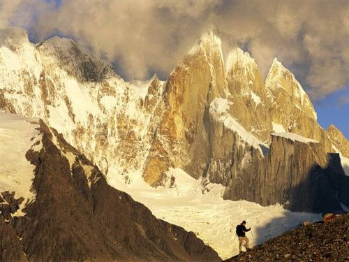 Camp and Hike A hiker climbs a rocky slope at the base of the jagged Cerro Torre Massif in the Patagonia region of southern Argentina