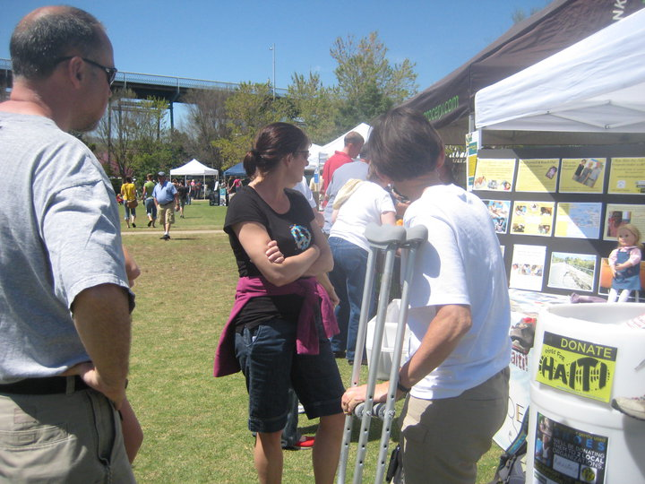 Guns and Military Dr. June Hanks discussing The Advantage Program and the Shoes for Haiti donation drive to a couple passing by the booth.