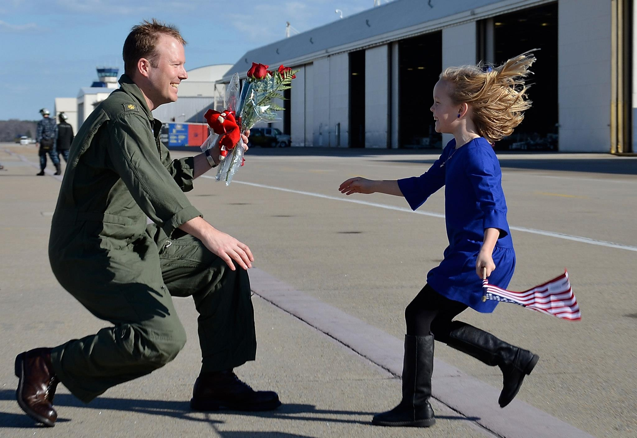 Guns and Military Lt. Cmdr. Pat Hart, assigned to Strike Fighter Squadron (VFA) 143, is reunited with his daughter during a homecoming celebration for the squadron.