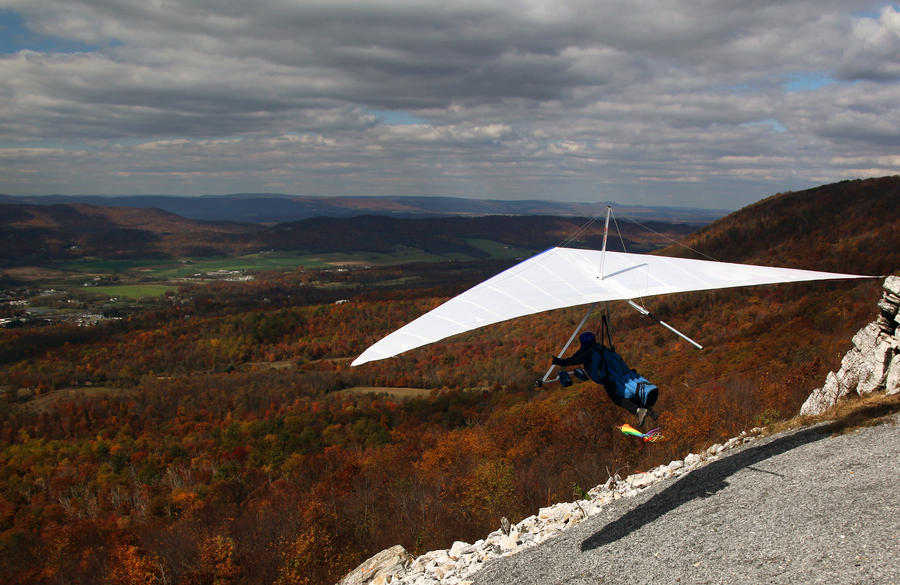 Extreme the rainbow colored windsock is straight out, fully deployed as this Hang Glider launches from a mountain top near Chambersburg, PA