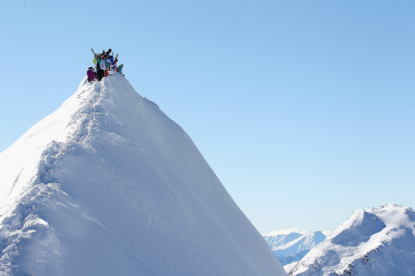 Ski Athletes study their lines as they prepare for descent --- what??