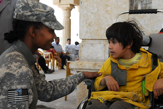 Guns and Military U.S. Army Pfc. Diamond Madison helps fit a pediatric wheelchair to a disabled child at the Anbar Operations Center, in Anbar province, Iraq