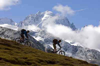 Two mountain bikers enjoy the snowcapped mountains near Chamonix, France.
