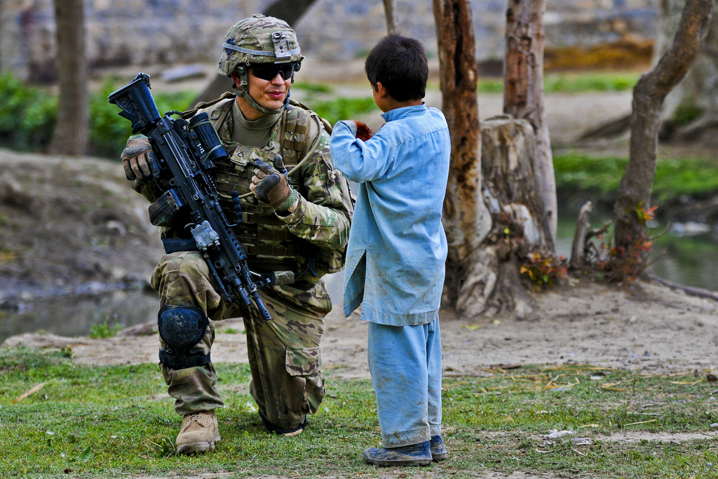 Guns and Military U.S. Army Pfc. Jared Baughn talks to an Afghan child