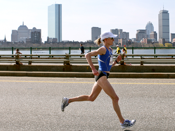 Fitness Deena Kastor runs with the Boston skyline behind her.