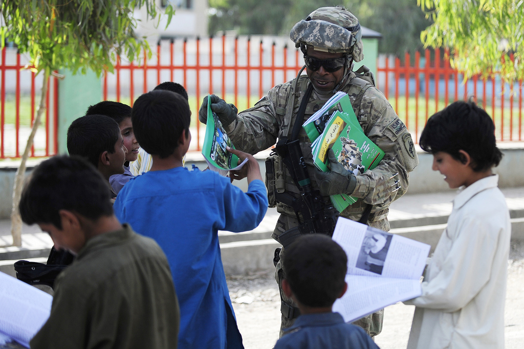Guns and Military U.S. Army Sgt. 1st Class Carl Coles, a Civil Affairs member of Provincial Reconstruction Team Farah, hands out magazines while greeting local children and other members of the community during a mission in Farah City, Farah province, Afghanistan May 7.