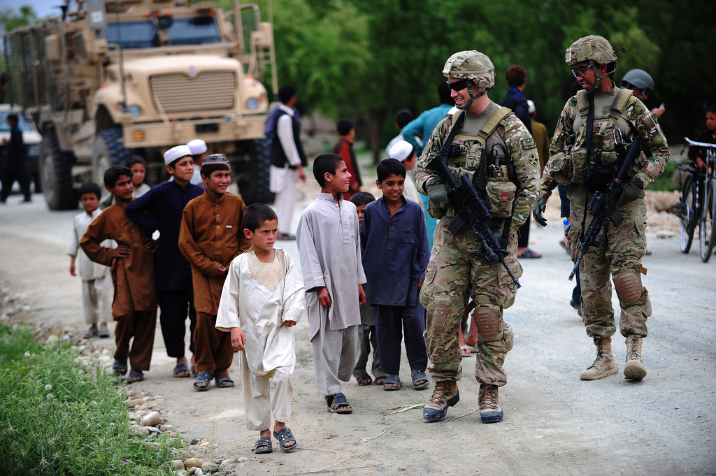 Guns and Military U.S. Air Force Capt. Hans Winkler and 1st Lt. Jasamine Pettie talk to children April 19, 2012, in Laghman Province, Afghanistan.