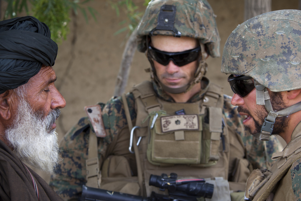 Guns and Military Ali, right, a linguist, and U.S. Marine Corps Lt. Col. David Bradney, center, the commander of the 1st Battalion, 7th Marine Regiment, Regimental Combat Team 6, speak with local Afghan man about the detainment of a suspected Taliban fighter in an adjacent