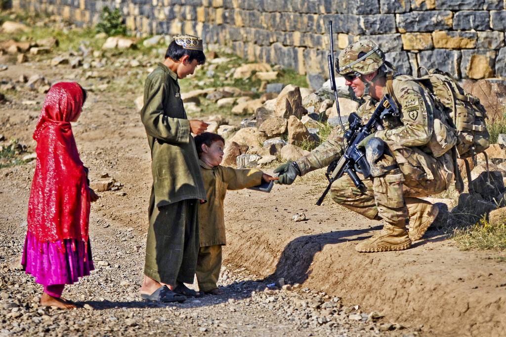 Guns and Military U.S. Army Cpl. Brian Lewis, a native of Duluth, Minn., and team leader assigned to 501st Infantry Regiment, 4th Brigade Combat Team (Airborne), 25th Infantry Division greats an Afghan boy while conducting a security patrol in Shaway Valley, June 2