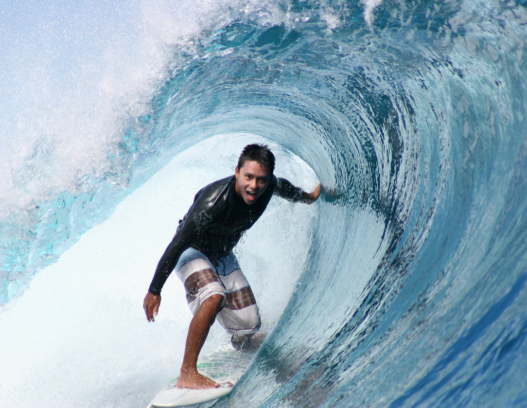 Surf Dennis Tihara surfing a tube at Teahupoo, Tahiti.