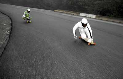 Skateboard Longboarders crouch into a turn on a road in Vancouver
