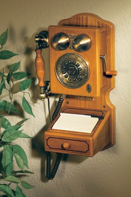 Capture all the allure of the early 1900s with a Crosley antique replica wall phone. Country Wall Phone is an exacting replica with a crank handle that really turns, and touch-tone buttons with a rotary look. The handcrafted oak veneer cabinet comes with brass-plated hardware and a storage compartment under the desk lid. Includes volume controls for ringer, receiver and is tone/pulse switchable, speaker phone and last number redial by pushing center of dial face. Dimensions: 12-1/4W x 17-1/2T x 7D. Color: Oak. Type: Wall Phones. - $89.99
