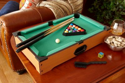 Entertainment Challenge friends and family to a game of pool on almost any table in the house. Unlike a normal billiards table, this tabletop version is affordable and portable enough to take with you on the road to parties and other social events. Details like the traditional felt-covered play surface and ball return add to the authentic look. Table easily stores out of the way when not in use. Includes two one-piece cues, full billiard ball set, table brush and chalk. Dimensions: 20L x 12.5W x 3.75H. - $39.99