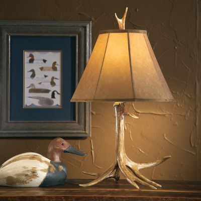Hunting By using shed natural antlers as the guide, the replicas used for our Antler Lamps are meticulously hand-cast using a high-quality resin, then hand-stained and hand-rubbed for a realistic look. The three-way, twist-switch lamp provides the perfect amount of light for a den or bedside table. The warm light cast from each lamp penetrates a handmade, faux-suede shade built around a steel skeleton. The inside of this oversized shade is lined with pongee. The One-Antler shade stands 10-1/2H, has a 7 top diameter and a 16 bottom diameter. Max 100-watt bulb. Imported. Measures: 25-3/4H x 14-1/2W. Color: Natural. - $49.99
