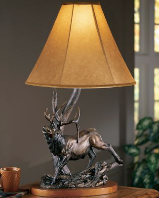 Hunting Master sculptor John Parsons amazing attention to realism is exemplified through perfect posturing and minute details. Every element of animal movement is captured as the artist skillfully projects natures drama and beauty in sculpture. You can almost hear the elk bugle as it lifts its head in perfect positioning. The lamp base is beautifully veneered for a rich look. A lined faux-suede shade emits warm, inviting light thats suitable for any room. The shade is reinforced by a steel skeleton. Constructed of cast poly-resin and hand-painted with a bronzed patina, the appearance of this lamp is truly magnificent. It is operated with a three-way twist switch and can accommodate bulbs (not included) up to 100 watts. Imported. Dimensions: 35H (with shade) x 16.73W x 11.5D. - $179.99