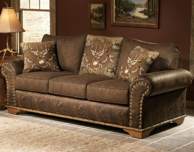 Entertainment Tastefully crafted for statement-making style, this classically inspired sleeper sofa brings class to any home. Its upholstered with an artful woodland tapestry that celebrates the sovereign journey of the majestic whitetail. A noble trophy buck is featured prominently, bordered with a frame of shed antlers and scenes of its growth. A plush fabric with a houndstooth pattern colored with deep greens and rich chocolate browns complements the whitetail montage. Lasting enjoyment is assured by kiln-dried, hardwood, fortress frame construction along with a high-density/high-resiliency cushion core that has fiber wrapping for total comfort. Deep brown faux leather trim with a distressed finish surrounds the piece and is balanced by a contrasting welt. Trimmed with Cabelas exclusive shotgun nails and hand-carved wood. A fold-away queen-sized bed comfortably sleeps two adults. Made in USA. 90L x 38D x 39H. Color: Chocolate. - $2,099.99