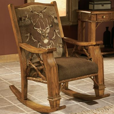 Entertainment Tastefully crafted for statement-making style, this inspiring rocking chair brings class to any home. Its upholstered with an artful woodland tapestry that celebrates the sovereign journey of the majestic whitetail. A noble trophy buck is featured prominently, bordered with a frame of shed antlers and scenes of its growth. A plush fabric with a houndstooth pattern colored with deep greens and rich chocolate browns complements the whitetail imagery. A kiln-dried hardwood fortress frame offers resilient durability. The machine-tied coil seat frame provides level comfort across the high-density, fiber-wrapped seat cushion. The hand-carved arms and back emulate the sturdy splendor of weathered boughs. Made in USA. 30L x 37D x 42H. Color: Chocolate. - $1,099.99