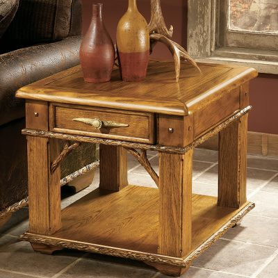 Entertainment Tastefully crafted for statement-making style, this beautiful hardwood side table brings class to any home. Kiln-dried, fortress frame construction offers resilient durability. Felt-lined drawer, hand-carved trim and faux antler resin handles. Dimensions: 28 L x 26 D x 24 H. - $699.99