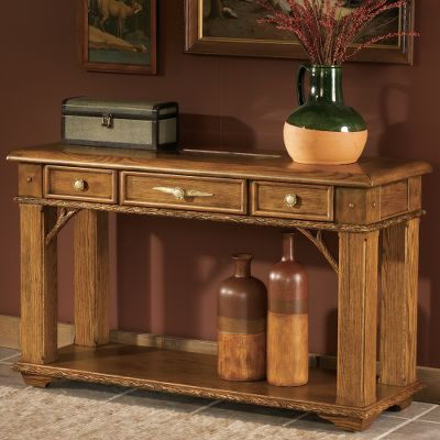 Entertainment Tastefully crafted for statement-making style, this beautiful hardwood sofa table brings class to any home. Kiln-dried, fortress frame construction offers resilient durability. It features a felt-lined display drawer, two smaller drawers, faux antler resin handles and hand-carved trim. A glass top allows the display of your favorite hunting or decorative memorabilia. 50L x 18D x 30H. - $899.99