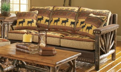 Hunting Bring the look of a vacation lodge to your home with this handcrafted, log-accented sofa. Handcrafted, authentic rustic poplar wood arms have a sunburst twig design. The fully upholstered seating area invites you to sit down in superb comfort. The patterned chenille fabric shows a bull moose, fish and forest leaves, all in nature-rich colors of tan, forest green, russet burgundy and black. Granite-colored, tweedlike chenille boxing fabric and chocolate brown faux leather for the body and contrast welting match nicely with the pattern. Hand-applied Cabelas nail trim is featured at the arms and base. Seat cushions are reversible to the chocolate brown faux leather. Includes a pair of throw pillows. Assembled with kiln-dried, fortress frame construction. Machine-tied coil seating unit and high-density, high-resiliency cushions with fiber wrapping provide level comfort across the seating area. Made in USA. 81L x 40D x 38H. Color: Forest Green. - $1,999.99
