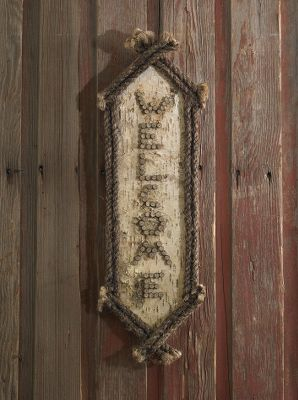 Greet guests with a rustic sign made of natural birch bark and rope accents. Delivered ready to hang. Each piece is unique.Dimensions: 26H x 7W. Type: Wood Signs. - $34.99