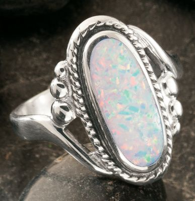 Entertainment This classic sterling silver womens ring features an oblong, man-made opal, which is more durable and consistent than natural opal. The single band splits at the setting, which is simply and beautifully surrounded with a dainty braided frame. Made in USA.Setting dimensions: 3/4L x 5/8W. Whole sizes: 4-10. - $79.99