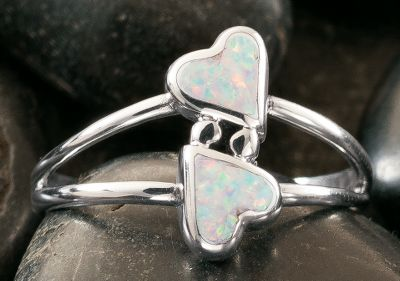 Entertainment Two fun and playful hearts hug in this sterling-silver ring from Silver Legends. Both hearts are inlaid with a sparkling man-made white opal, which is more durable and consistent than natural opal. Made in USA. Dimensions: 3/4L x 1/2W. Whole sizes: 4-9. - $49.99