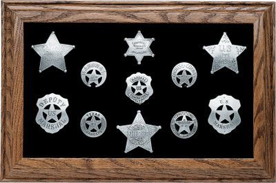 This display makes a perfect gift for the lawman in the family or a great display in the Cowboy-Action Shooters den. These 11 silver-plated replica badges include Tombstone Sheriff, U.S. Marshall and Texas Ranger among many others. The badges have a hand-applied tarnish so they look authentic. Badges are securely attached to the board and surrounded by a richly colored felt background, housed in a beautiful hardwood frame with glass front. Dimensions: 11-1/4H x 17-1/2W. Type: Display Boards. Type: Display Boards. Lawman Badge Board. - $199.99