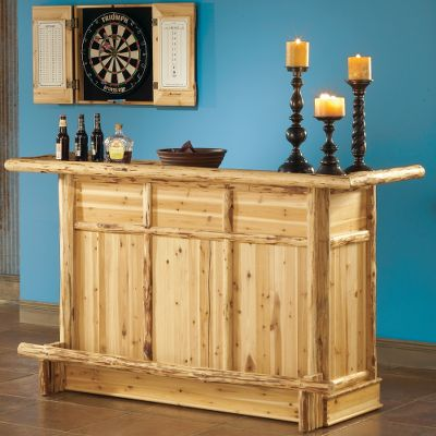 "Entertainment You'll have more reasons to stay at home after you create your entertainment haven. Assemble the ultimate game room with these price-friendly furniture and game pieces. Each solid pine item is made from the finest grade logs, handpicked and handcrafted - so no two are alike. Sixty-day kiln-drying process and uneven-textured skip-peel finish give it an authentic, rustic look that's both functional and attractive. So go ahead and build the ultimate fun-filled environment complete with the works. Your family won't want to leave, and your friends will want to stay. Relax with a drink in hand or play a game of cribbage on this stunning handcrafted log bar. Wine bottles, glasses and dice cups are just a few of the things you can store in this well-crafted piece. Includes two cupboards with doors, two shelves, wine rack and glass holders. Limited one-year manufacturer's warranty. Dimensions: 71-1/2""L x 25-3/4""W x 43-1/2""H. Type: Bar Furniture. - $1,299.99"