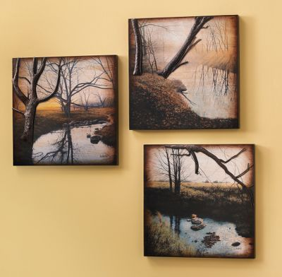 The foremost trees in these landscapes are featured as metal bas-relief sculptures sitting out in front of their backgrounds adding depth and an extra spark of interest to these tranquil scenes. This set of three wall art plaques arrives ready to hang and rearrange as you like. No framing required. Dimensions: 18H x 18W x 1-1/2D per panel. - $199.99