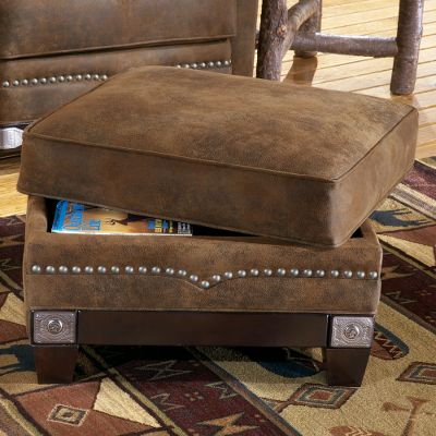 Entertainment Capture a piece of America's Western history right in your own living room. The exclusively licensed Winchester storage ottoman has a rich brown, microdenier fabric to give it the look and feel of leather and provides durability that will last for years. Extra storage space is perfect for tight living rooms. The fabric has hand-applied, etched- and nailed metal applique and nail trim, including several Winchester nails. The storage ottoman will match either the sofa, love seat or chair with the large decorative nails. Kiln-dried, hardwood frame construction. Limited lifetime warranty. Made in USA. Dimensions: 28 L x 24 D x 19 H. Color: Brown. - $699.99