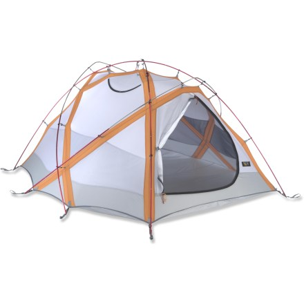 Camp and Hike The Mountain Hardwear Trango 2 tent is designed for winter mountaineering. It's built incredibly strong and engineered for the toughest high alpine conditions. 2 mesh/fabric doors provide easy entry/exit; large vestibule provides work-worthy space while a small vestibule is handy for access, overflow storage and vent manipulation. Mountain Hardwear Trango 2 is strong and easy to set up; front vestibule pole quickly affixes to the outside of the tent via pole clips. Evolution Tension Arch(TM) technology multiplies structural aspects of the tent skeleton without adding poles or heavy wall fabric. Stiff but lightweight fabric spreads the load-bearing capability of the poles over a wide surface area; ribbed wall fabric adds strength while remaining lightweight. DAC Featherlite(R) poles have a high strength-to-weight ratio, use extrusions, not inserts, to minimize breakage and are anodized without the use of harmful acids. Guaranteed watertight construction with fully taped fly, taped perimeter seams, welded corners and welded guy clip anchors. 2 clear SVX windows are placed correctly to check the weather; tent's color fends off depression while you wait for the weather to improve. Dry-entry vestibule design prevents water from dripping inside tent when vestibule is open, improving livability. Mesh/fabric zippered thru-vent ensures good air circulation. Expedition bathtub-style nylon floor features a non-hydrolyzing, 3000mm-rated polyether urethane coating and Durable Water Repellent finish for waterproofness and durability. For extra stability each guyout point clips to the frame on the interior side of the rainfly via welded attachment points. Catenary-cut seams create a taut canopy and rainfly for improved strength. All the poles are color coded to the bar tacks in the webbing of the grommet tabs, plus reflective starter points help setup in low light conditions. - $439.93