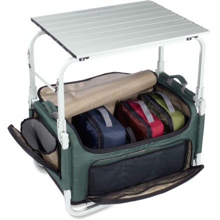 Camp and Hike With the REI Pack-N-Prep tote/table you're always ready to hit the road! It keeps all your camp kitchen items organized and accessible so you can whip up a meal that will satisfy the whole group. Aluminum roll-top table provides space to prep and cook food; table measures 22.5 in. x 18.25 in. and is sized to fit most 2-burner camp stoves (sold separately). Rugged polyester main bag offers ample space for packing food and kitchen supplies. Includes 3 organizer bags that fit tableware and cooking utensils (sold separately); bags have mesh tops and fit neatly inside the main bag. Store cleaning supplies in the exterior wet/dry pocket; store fuel bottles and other items (not included) in the outside pockets. Keep a roll of paper towels (not included) handy on the rod located on the side. Divider inside the main bag can be removed and hung from the frame to double as a caddy that keeps cooking utensils and cleaning supplies within reach. Aluminum tabletop stores inside the main bag when not in use. Powder-coated aluminum tubing and a molded foam base support the load; aluminum tubes and metal hardware resist rust. Dual side handles let you easily haul the REI Pack-N-Prep tote/table from the garage to the car to the campsite. - $129.00
