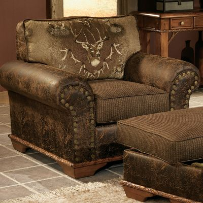 Entertainment Tastefully crafted for statement-making style, this inspiring chair brings class to any home. Its upholstered with an artful woodland tapestry that celebrates the sovereign journey of the majestic whitetail. A noble trophy buck is featured prominently, bordered with a frame of shed antlers and scenes of its growth. A plush fabric with a houndstooth pattern colored with deep greens and rich chocolate browns complements the whitetail montage. Lasting enjoyment is assured by kiln-dried, hardwood, fortress frame construction along with a high-density/high-resiliency cushion core that has fiber wrapping for total comfort. Deep brown faux leather trim with a distressed finish surrounds the piece and is balanced by a contrasting welt. Trimmed with Cabelas exclusive shotgun nails and hand-carved wood. Made in USA. 46L x 38D x 39H. Color: Chocolate. - $1,099.99